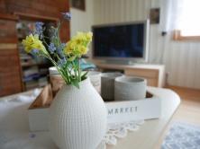 Valgeks värvitud laudis toob tuppa valgust ja laseb sel suuremana paista. Esiplaanil oma aia lilled lihtsas vaasis (Home4You), kandik ja küünlajalad HM Home.