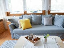 Valgeks värvitud laudis toob tuppa valgust ja laseb sel suuremana paista. Rustikaalsust rõhutavad tumedamast puidust aknaraamid. Esiplaanil oma aia lilled lihtsas vaasis (Home4You), kandik ja küünlajalad HM Home, tassid pererahva kogust. Ikea diivanvoodi Holmsund, kollane padi Jyskist, vaip HM Home