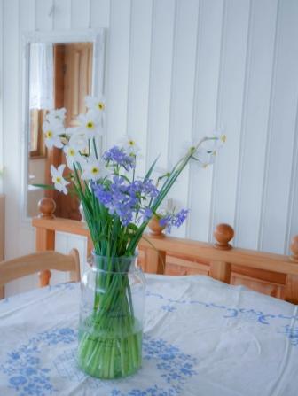 Valgeks värvitud laudis toob tuppa valgust ja laseb sel suuremana paista. Esiplaanil oma aia lilled lihtsas vaasis (u. 4 EUR, Koduextra), Peegel Jyskist, laudlina vanaema kollektsioonist